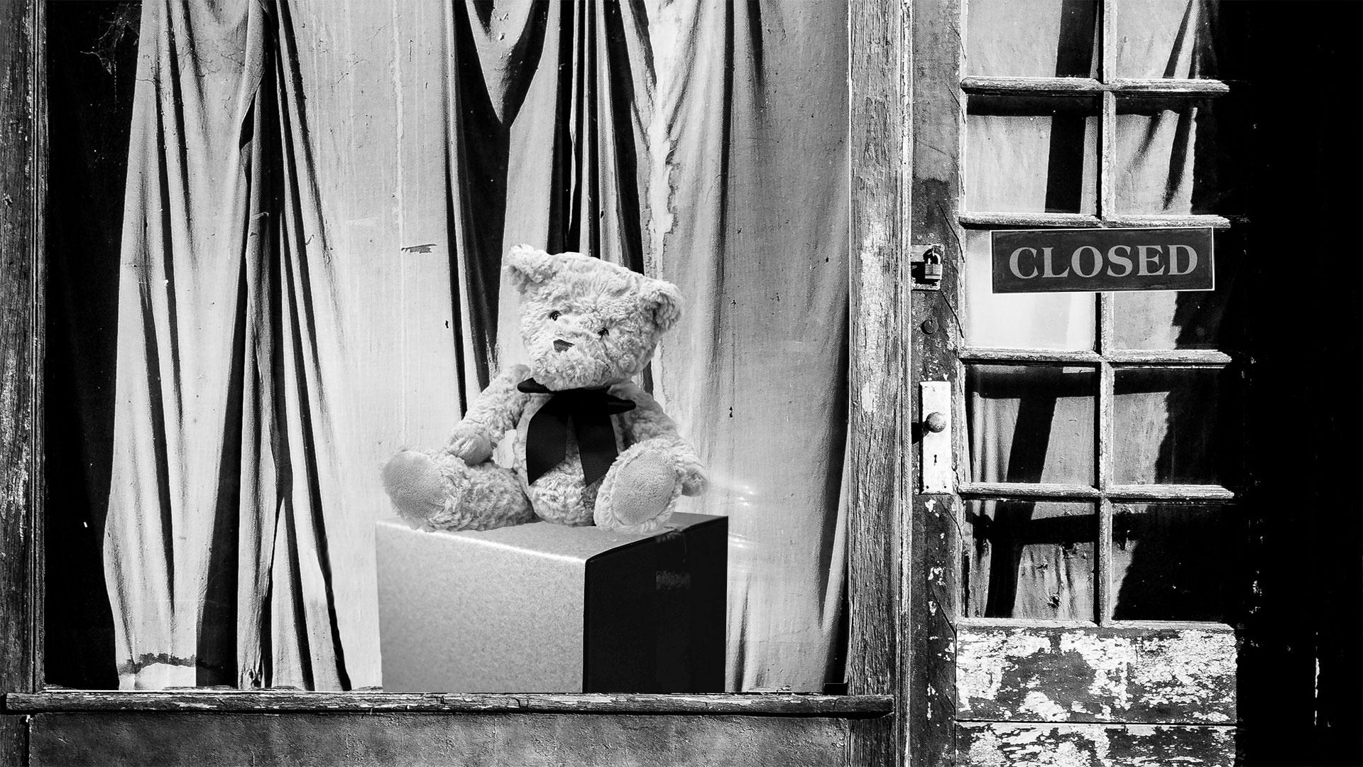 Geschlossener Detailhandel mit einem Teddybär im Schaufenster